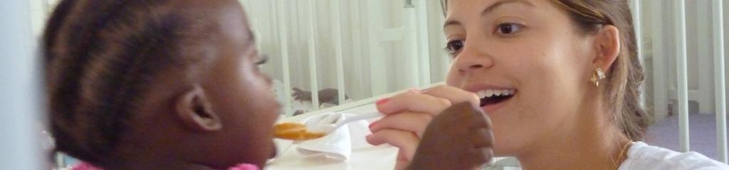 Volunteer füttert Kind in Kapstadt